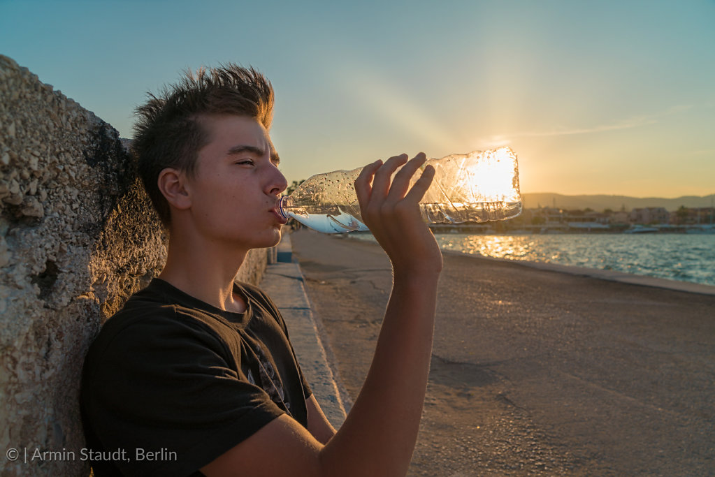 young man drinking water with the sun behind the bottle