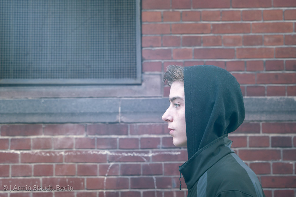 portrait of a young man in profile with hoodie