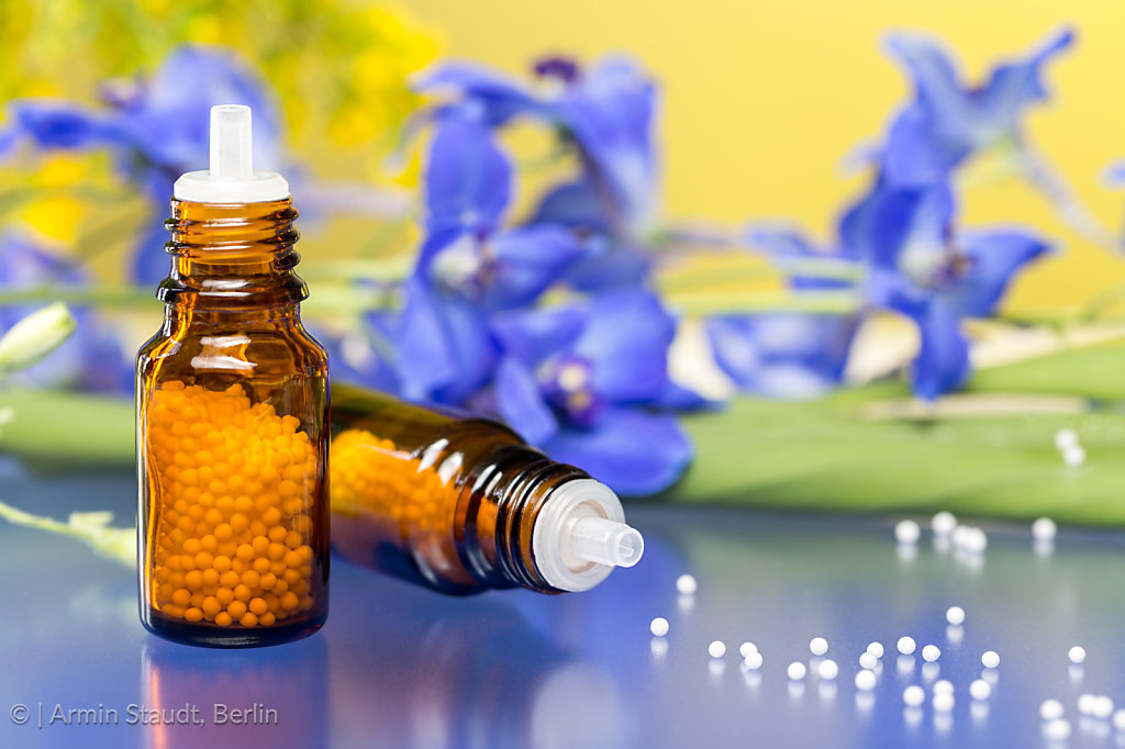two bottles with homeopathy globules and flowers, with blue reflecting underground