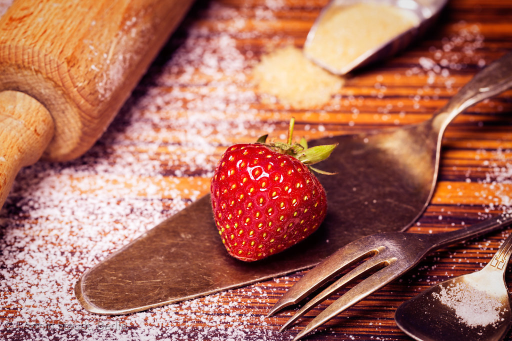 grandma's kitchen with strawberries, sugar, rolling pin, and silverware