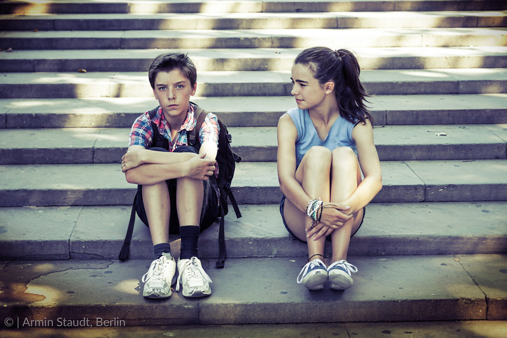 tired travelling siblings sitting on steps