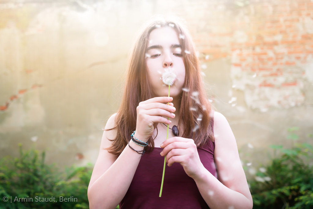 Pretty girl blowing dandelion in front of an old wall