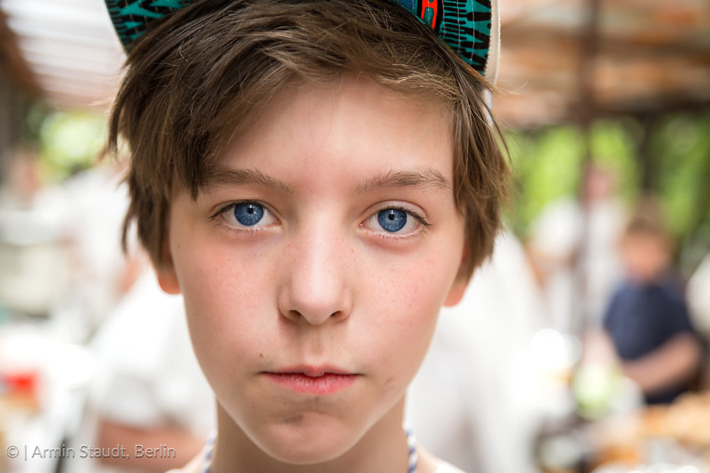 young boy with basecap looking into the camera, blurred people i