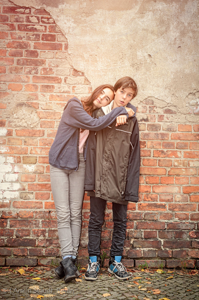 siblings arm in arm in front of an old brick wall