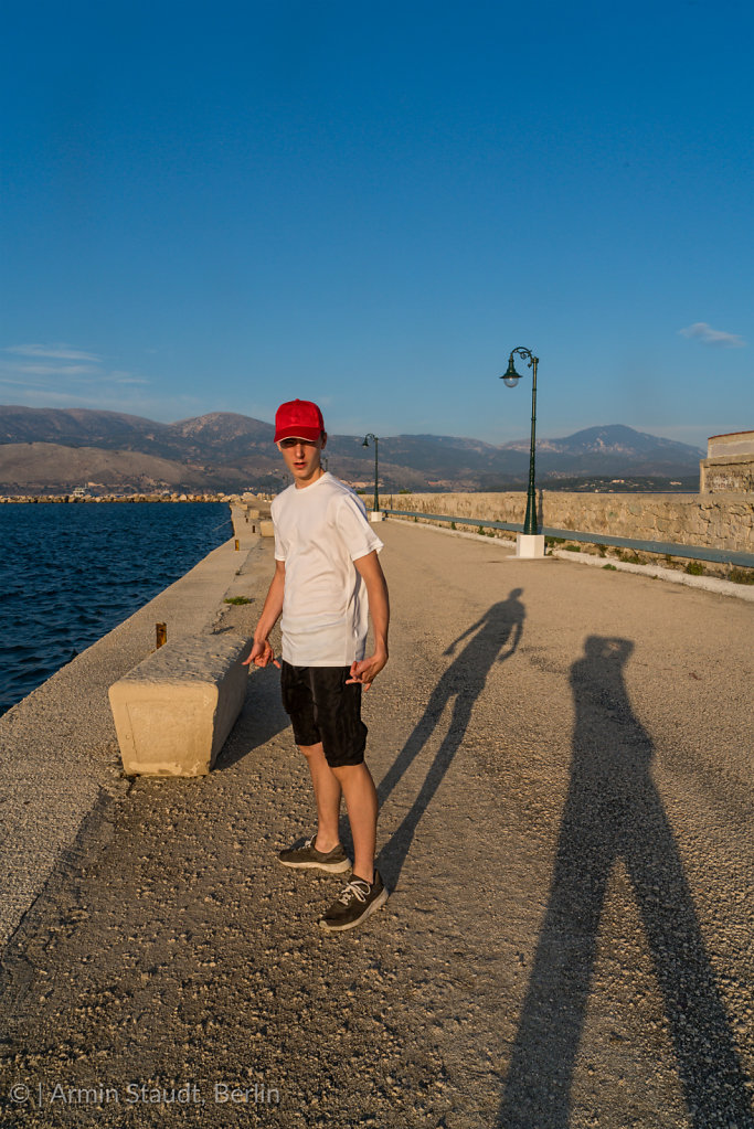 young man on vacation with the shadow of the photographer