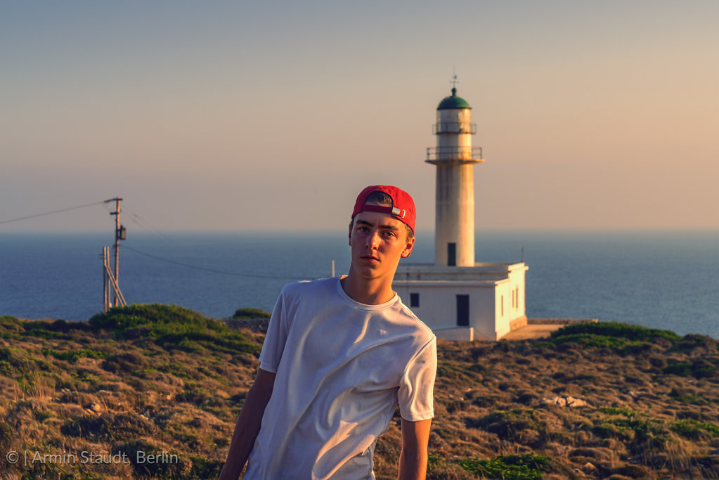 portrait of a young man in front of a lighthouse in Greece