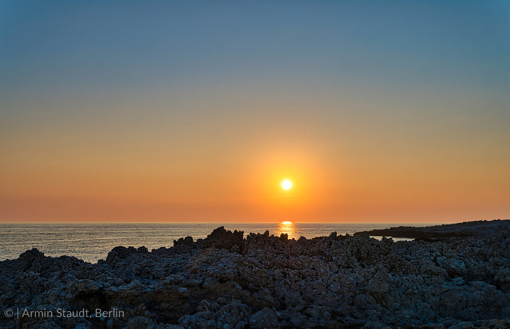 sunset over the sea with rough rocky shore