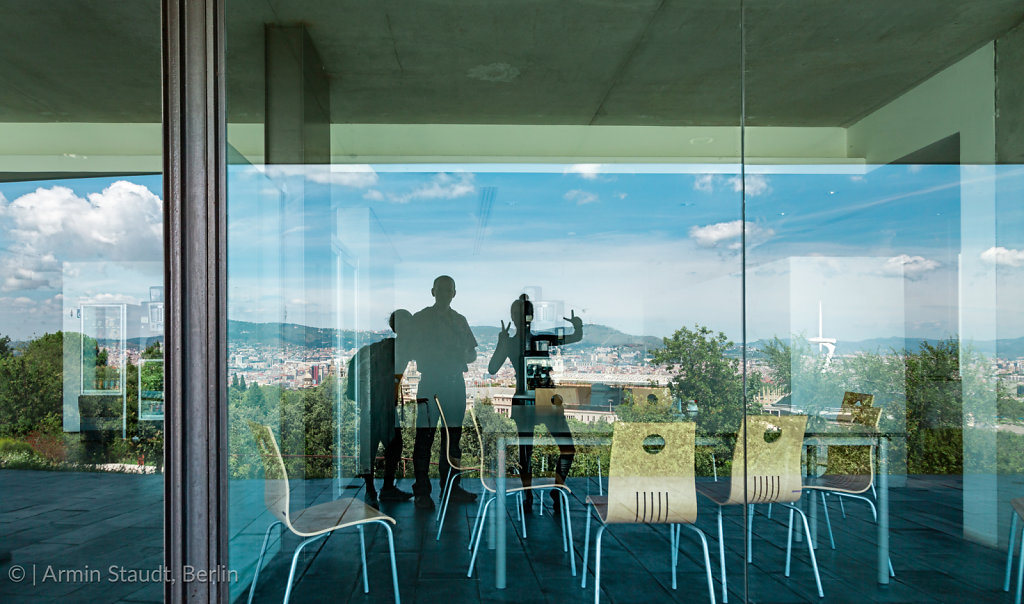 Barcelona mirroring in a window with three persons