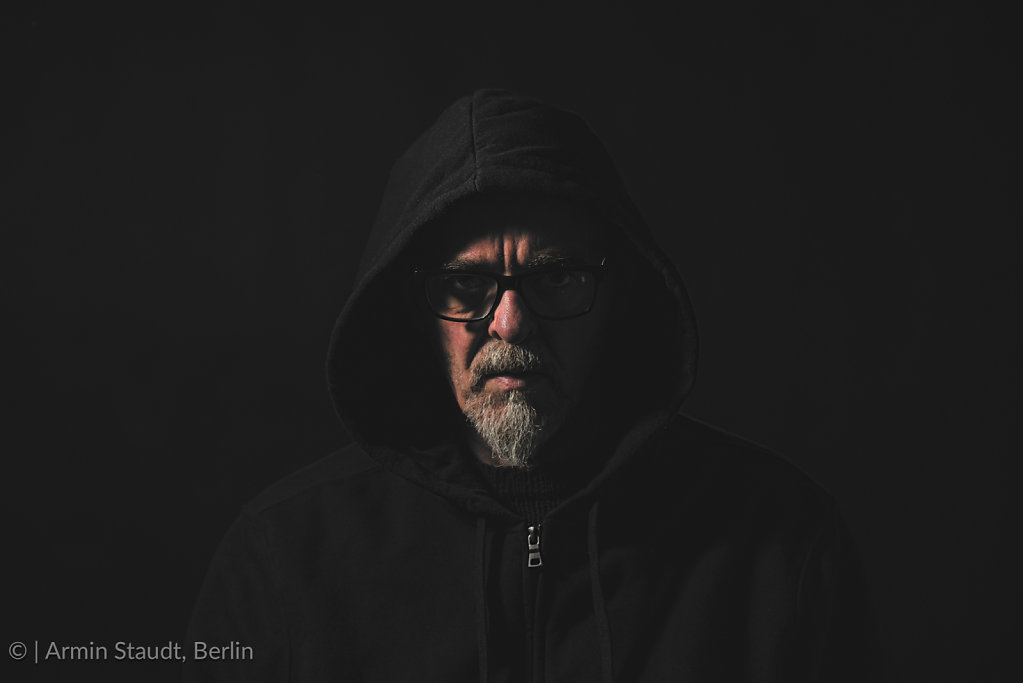 dark portrait of a man with gray beard , hoodie and glasses
